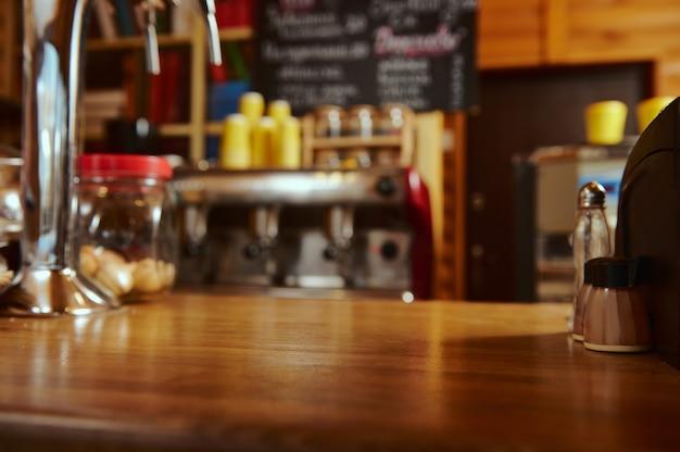 プロのコーヒーマシンを備えたインテリアコーヒーショップ。カフェ、カフェテリア、木製バー