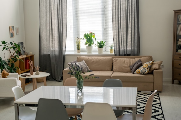 Interior of comfortable domestic room in a flat or house with table in the center surrounded by chairs, couch with cushions and armchair