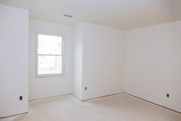 白い壁の空のアパートの住宅の内部建設