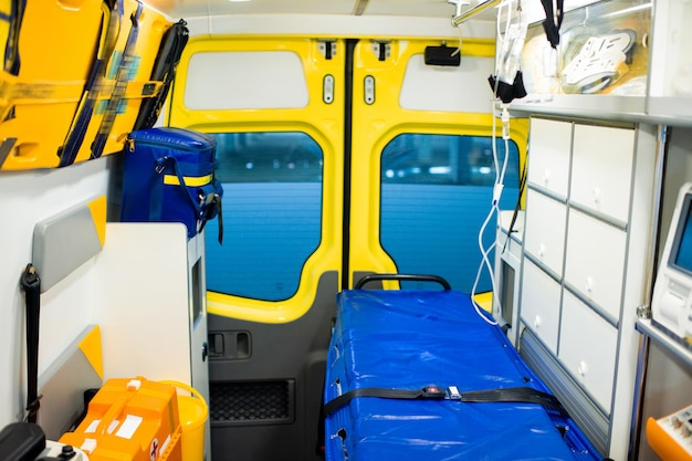 Interior of contemporary ambulance car with stretcher, dropper, first aid kit and other medical equipment