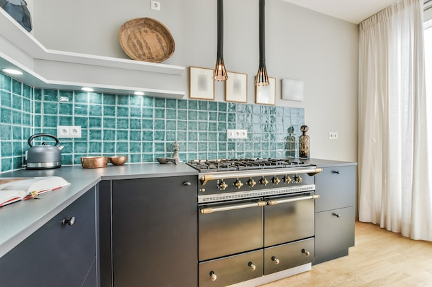 Interior of contemporary kitchen with minimalist style furniture and gas stove in light apartment