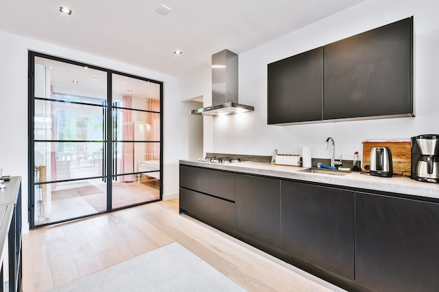 Interior of contemporary kitchen with stylish black cupboards and appliances near dining area in contemporary apartment