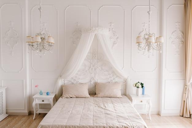 Интерьер современной бело-бежевой уютной спальни. просторная спальня с белой стеной и кроватью. городской современный дизайн комнаты.