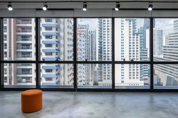 Interior of coworking space with spotlight and crownded building at business district
