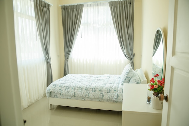 Interior of cozy bedroom in modern design with vase on white wood table.