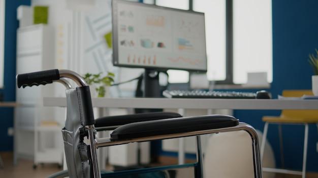 Interno di un'accogliente sala aziendale leggera con sedia a rotelle parcheggiata vicino alla scrivania
