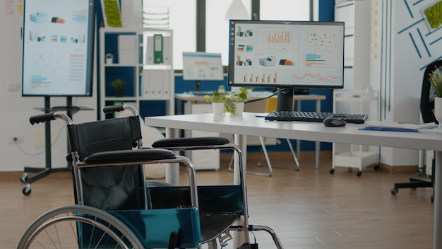 Interior of cozy light company room with wheelchair parked near desk