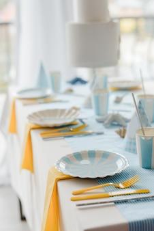 室内装飾、白い食器、黄色のカトラリー、ブルーのテーブルクロスを備えたテーブルセッティング。誕生日パーティーの装飾。セレクティブフォーカス。