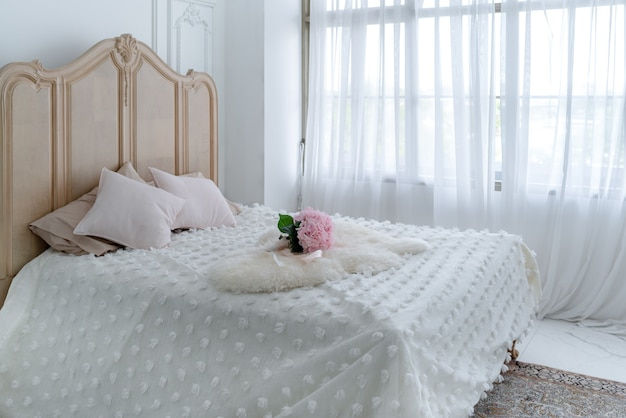 Interior or decoration of bedroom with pik pillows and flower bouquet in hotel