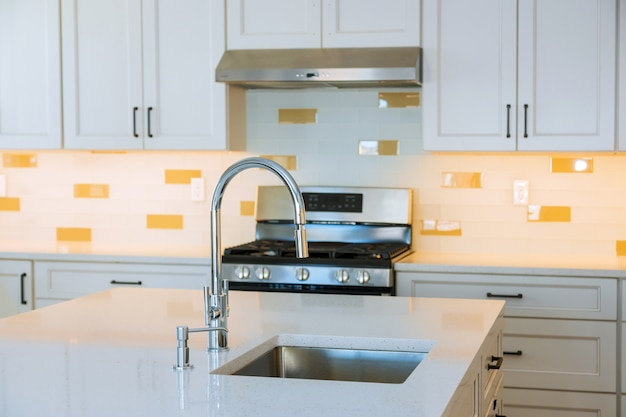 Interior design bright modern kitchen with stainless steel appliances with island sink