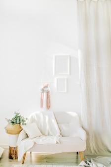 인테리어 디자인 컨셉. 흰 벽, 짚 바구니 속의 유칼립투스, 의자 및 커튼이있는 밝은 객실입니다.