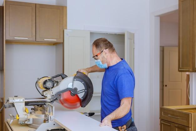 Работает над дизайном интерьера кухни с установщиком шкафов, устанавливающим предметы домашнего обихода, надев работники в медицинской маске для предотвращения covid-19 - это работает