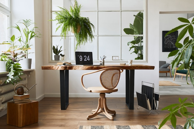 Interior design of home office space with stylish wooden desk, beautiful chair, laptop, platns, book and elegant personal accesories in cozy home decor.