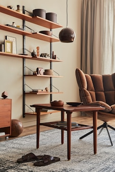 Interior design of living room with brown armchair, coffee table, wooden shelf, book, picture frame, decoration and elegant personal accessories in home decor..