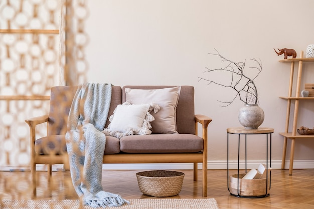 Interior design of living room with stylish brown wooden sofa, macrame, bookstand, lamp, coffee table, plants, decoration and elegant accessories. beige and japandi concept. template.