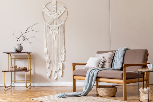 Interior design of living room with stylish brown wooden sofa, macrame, bookstand, lamp, coffee table, plants, decoration and elegant accessories. beige and japandi concept. .