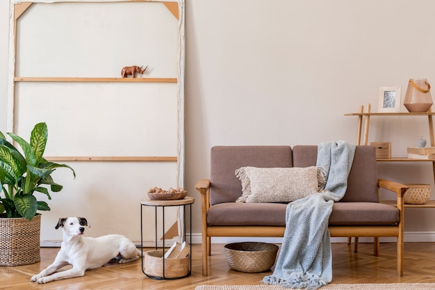 Interior design of living room with stylish brown wooden sofa, macrame, bookstand, lamp, coffee table, plants, decoration and elegant accessories. beige and japandi concept.