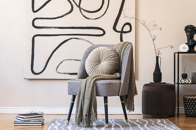 Interior design of living room with stylish gray armchair, abstract paintings on the wall, flowers in vase, pillow, plaid and elegant personal accessories. beige concept. modern home staging.