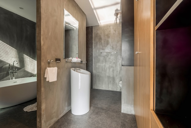 Interior design loft style in luxury bathroom features basin and bathtub, toilet in the house