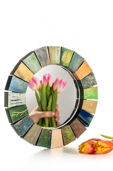 Interior design mirror handmade in wooden frame with bouquet of spring tulips
