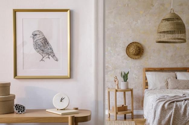 모형 액자, 나무 콘솔, 식물, 시계 책, 등나무 장식 및 세련된 가정 장식의 우아한 액세서리를 갖춘 침실의 인테리어 디자인.