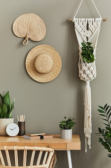 スタイリッシュなアームチェア、木の机、家の植物、サボテン、ラタンの装飾、マクラメ、時計を家に飾った、自由奔放に生きるリビング ルームのインテリア デザイン。植物学のホームオフィス。