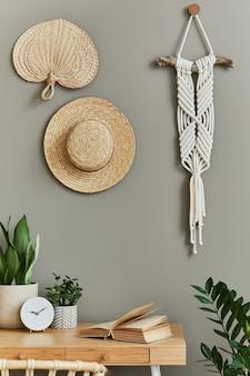 スタイリッシュなアームチェア、木製の机、観葉植物、サボテン、籐の装飾、マクラメ、家の装飾の時計を備えた自由奔放に生きるリビングルームのインテリアデザイン。植物学のホームオフィス。