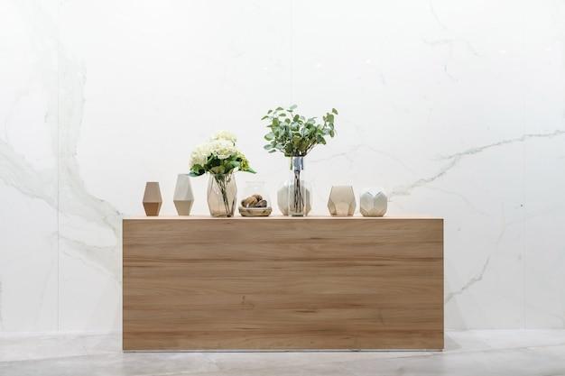 花瓶の美しい花と木製テーブルの装飾と古典的な部屋のインテリアデザイン