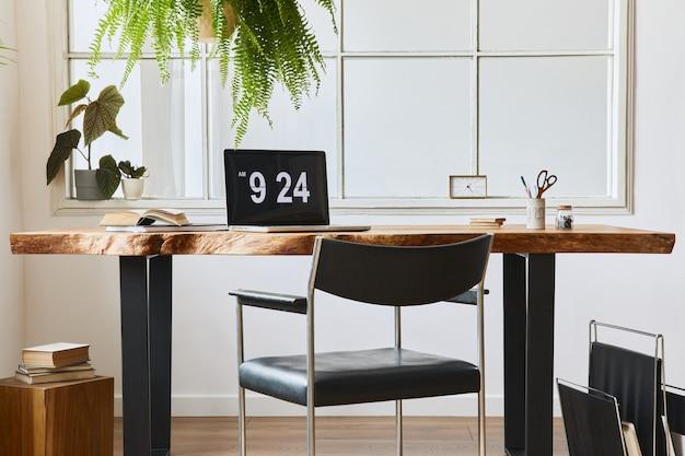 スタイリッシュな木製デスク、美しい椅子、ラップトップ、プラトン、本、居心地の良い家の装飾のエレガントなパーソナルアクセサリーを備えたホームオフィススペースのインテリアデザイン。