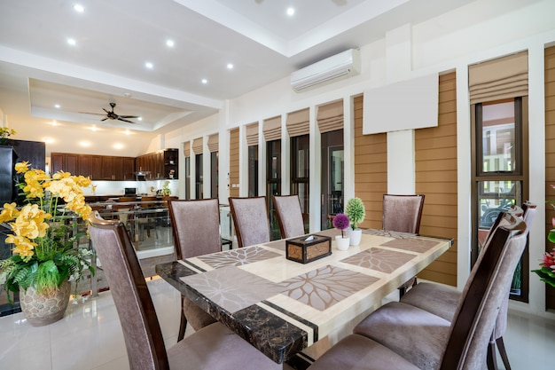 Дизайн интерьера дома, дома и виллы включает обеденный стол, обеденный стул и желтый искусственный цветок в большом горшке.
