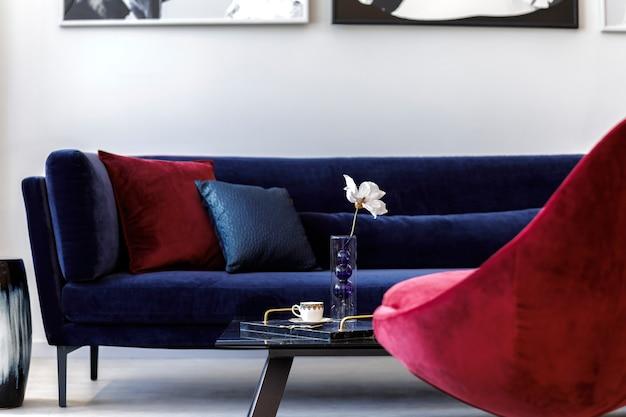 Дизайн интерьера гостиной с синим бархатным диваном, красным креслом, картинами, дизайнерской вазой, столом и декором, бетонным полом.