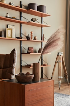 茶色のアームチェア、コーヒーテーブル、木製の棚、本、額縁、装飾、家の装飾のエレガントなパーソナルアクセサリーを備えたリビングルームのインテリアデザイン。
