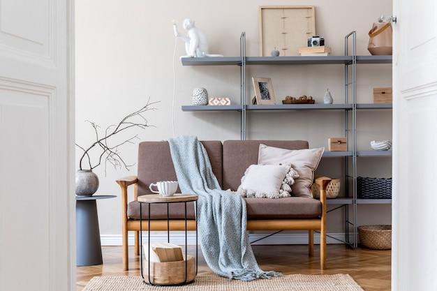 갈색 나무 소파, 회색 책꽂이, 커피 테이블, 격자 무늬, 베개, 장식 및 우아한 액세서리가있는 거실의 인테리어 디자인. 베이지와 japandi 개념. 세련된 홈 스테이징.