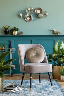 세련된 안락 의자, 식물이있는 금 냄비, 세련된 장식, 카펫 및 우아한 개인 액세서리가있는 거실의 인테리어 디자인. 가정 장식을 디자인하십시오. 선반이있는 녹색 벽 패널. 주형.