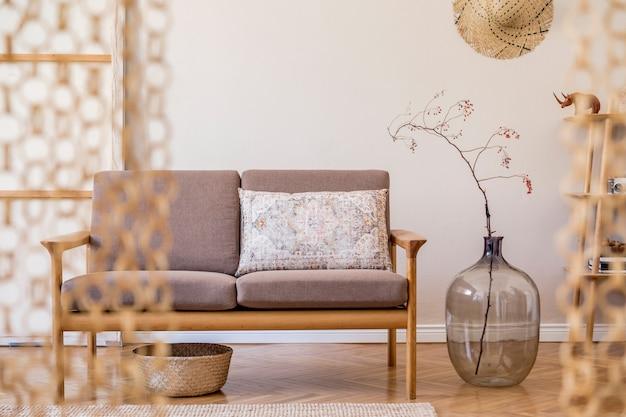 スタイリッシュな茶色の木製ソファ、マクラメ、本立て、ランプ、コーヒーテーブル、植物、装飾、エレガントなアクセサリーを備えたリビングルームのインテリアデザイン。ベージュとjapandiのコンセプト。レンプレート。