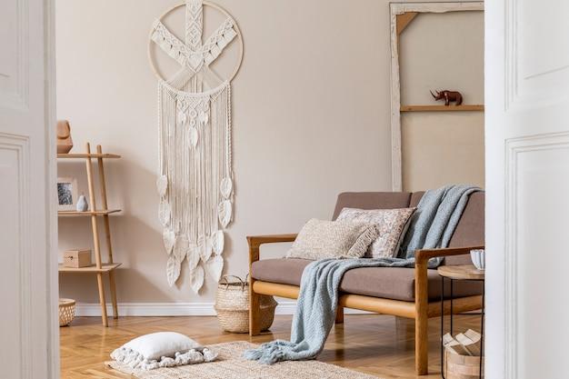 Дизайн интерьера гостиной со стильным коричневым деревянным диваном, макраме, книжной стойкой, лампой, журнальным столиком, растениями, украшениями и элегантными аксессуарами. концепция бежевого и японского.