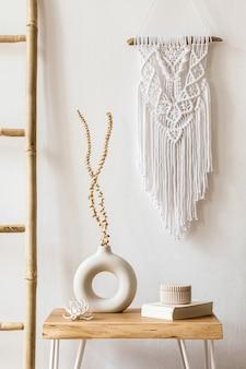 Дизайн интерьера гостиной со стильными засушенными цветами в вазе, деревянной лестницей, пледом, белым макраме и личными аксессуарами в домашнем декоре.