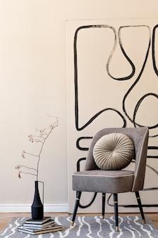 세련된 회색 안락 의자, 벽에 추상 회화, 꽃병에 꽃, 베개, 격자 무늬 및 우아한 개인 액세서리가 있는 거실의 인테리어 디자인. 베이지 컨셉입니다. 현대 홈 스테이징. 주형