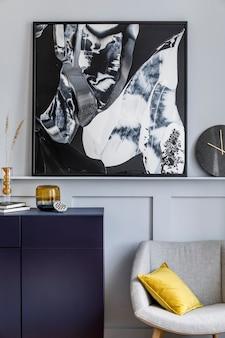세련된 네이비 블루 옷장, 회색 안락 의자, 베개, 검은 색 시계, 말린 꽃, 현대 회화, 장식 및 가정 장식의 우아한 액세서리가있는 거실의 인테리어 디자인.