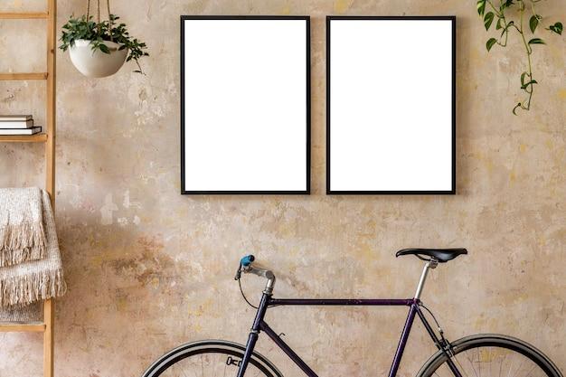 두 개의 검은색 포스터가 있는 거실의 인테리어 디자인은 프레임, 자전거, 화분에 심은 식물을 조롱합니다. 그런 지 와비 사비 벽입니다. 세련된 힙스터 가정 장식. 주형.