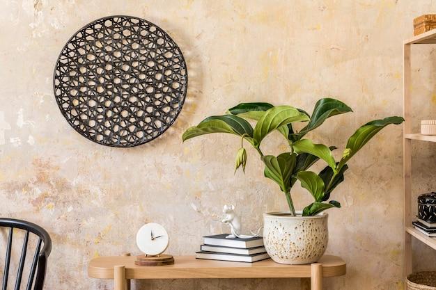Дизайн интерьера гостиной с деревянной консолью, полкой, книгами, растениями, черным стулом, украшениями и элегантными личными аксессуарами в домашнем декоре ваби саби.