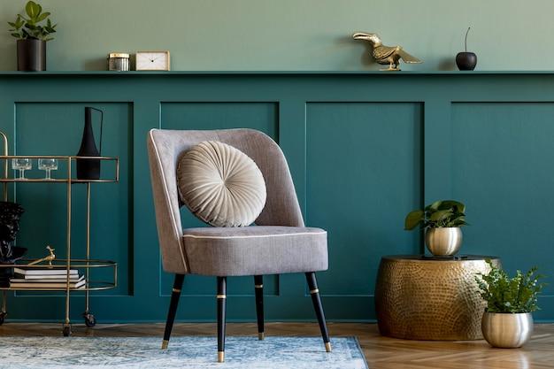 세련된 안락 의자, 금색 주류 캐비닛, 많은 식물 및 우아한 개인 액세서리가 있는 고급스러운 거실의 인테리어 디자인. 선반이 있는 녹색 벽 패널. 현대 가정 장식입니다. 주형.