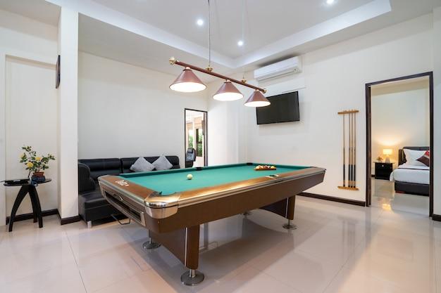 Дизайн интерьера современного дома, дома, виллы с бильярдным столом, полкой, диваном и телевизором в гостиной