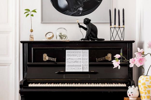 モックアップ絵画、スタイリッシュな黒のピアノ、空気植物、ランプ、花瓶の花、金の時計、居心地の良い家の装飾のエレガントなパーソナルアクセサリーを備えたモダンなリビングルームのインテリアデザイン。