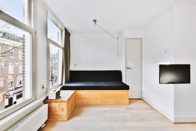 Дизайн интерьера современной гостиной в стиле минимализма с большими окнами, деревянным диваном, шкафом и телевизором на белой стене