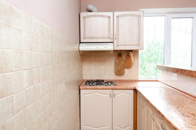 白い現代的な家具、壁にベージュのセラミックタイル、ガスストーブ、窓の景色を望むモダンで狭いスマートコンパクトキッチンのインテリアデザイン。