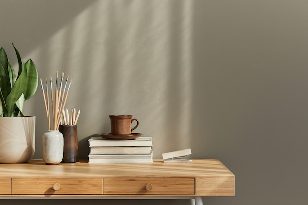 スタイリッシュなデスク、ラン、本、装飾、事務用品、コーヒー、コピー スペース、メモ、個人的なアクセサリーを備えた中立的なボヘミアン リビング ルームのインテリア デザイン。