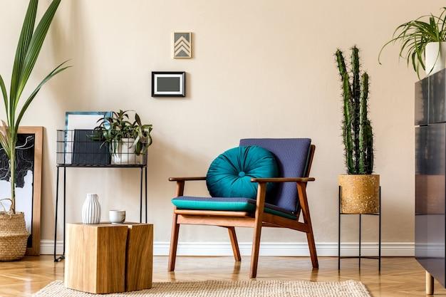 세련된 블루 네이비 화장실, 선인장, 디자인 안락 의자, 주최자, 장식 및 우아한 개인 액세서리가있는 복고풍 현대 거실의 인테리어 디자인. 세련된 가정 장식.