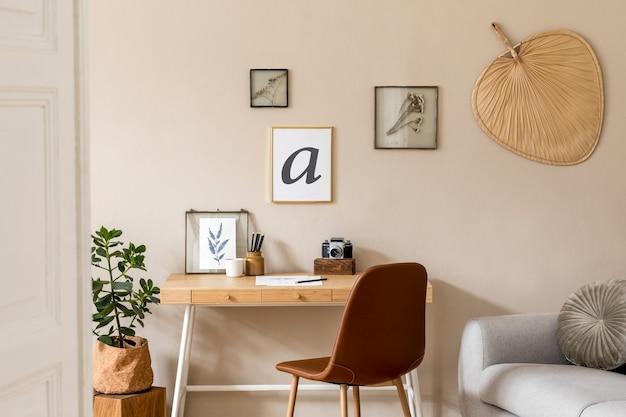 사진 프레임, 나무 책상, 회색 소파, 식물, 책 사무실 및 개인 액세서리를 모의로 한 스칸디나비아 열린 공간의 인테리어 디자인. 세련된 중립 가정 장식. 베이지 색 벽. 주형.