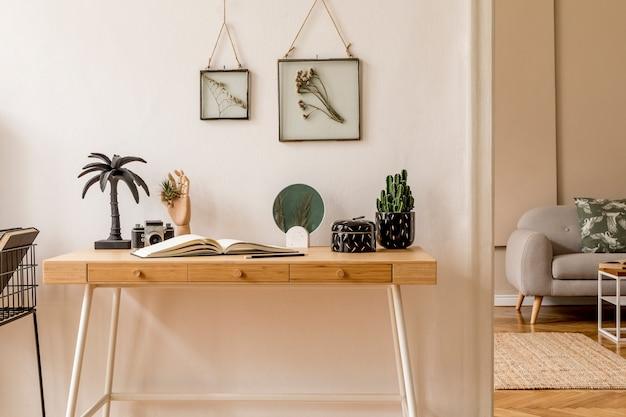 Дизайн интерьера скандинавского open space с фоторамками, деревянным столом, серым диваном, кактусами, книжным офисом и личными аксессуарами. стильная нейтральная домашняя постановка. бежевые стены.